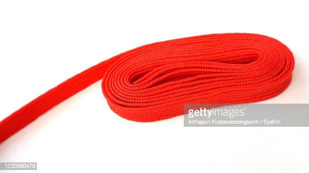 close-up of red strap against white background - strap stock pictures, royalty-free photos & images