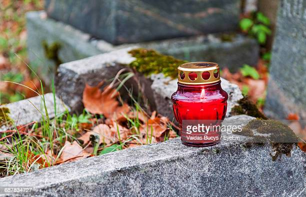 close-up of red tea light candle on cemetery - grab stock-fotos und bilder