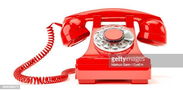 Close-Up Of Red Telephone On White Background