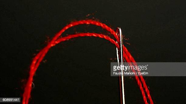 Close-Up Of Red Thread Going Through Needle Against Black Background