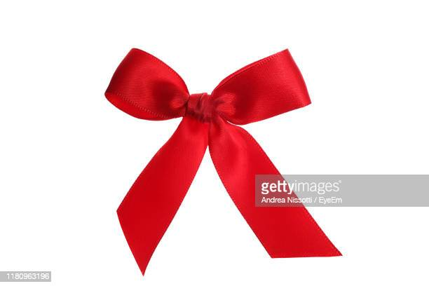 close-up of red tied bow against white background - tied bow stock pictures, royalty-free photos & images