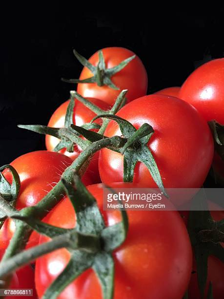 Close-Up Of Red Tomatoes Against Black Background