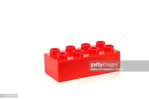 close-up of red toy block over white background - objet rouge photos et images de collection
