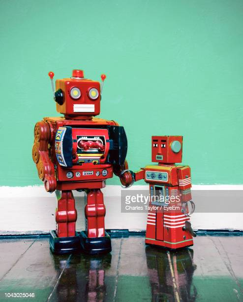 close-up of red toy robots on floor against wall - toy stock pictures, royalty-free photos & images