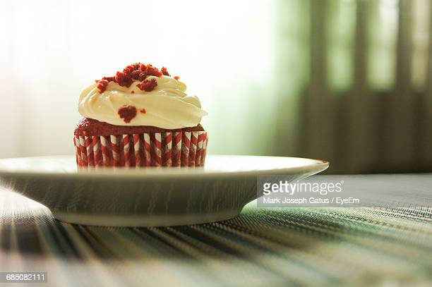 Close-Up Of Red Velvet Cupcake With Cream Cheese Frosting On Table