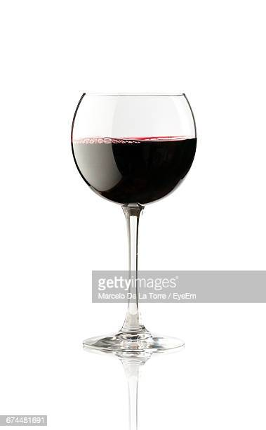 close-up of red wine against white background - drinking glass stock pictures, royalty-free photos & images