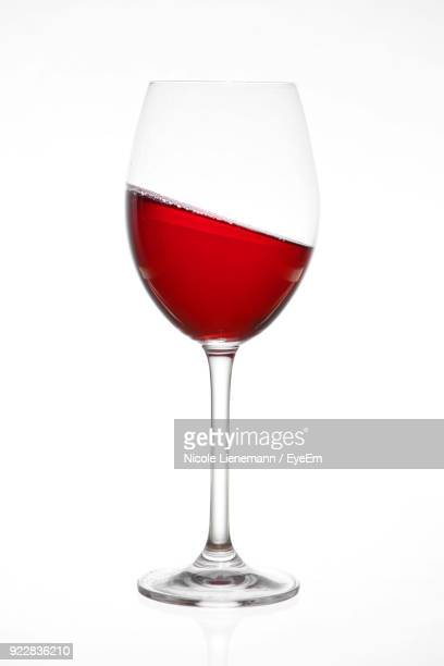 close-up of red wine against white background - wineglass stock pictures, royalty-free photos & images