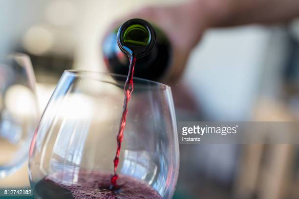Close-up of red wine being poured in from a bottle into the glass.