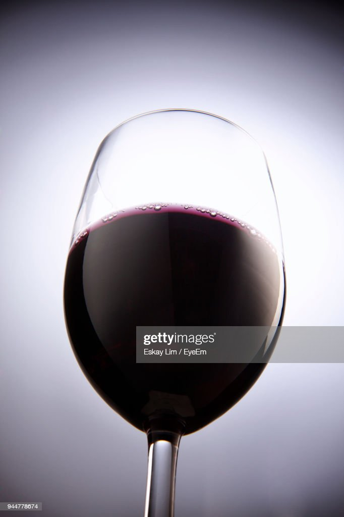 Close-Up Of Red Wine In Wineglass Against White Background : Stock Photo
