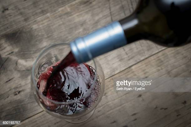 close-up of red wine pouring from bottle in glass on table - transbordar imagens e fotografias de stock
