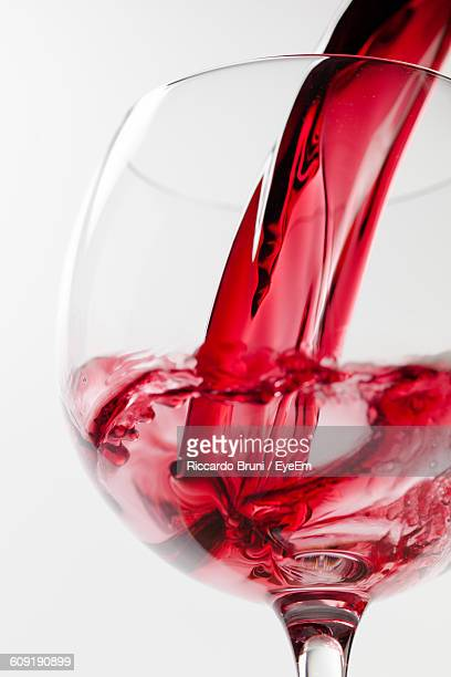 Close-Up Of Red Wine Pouring In Glass Against White Background