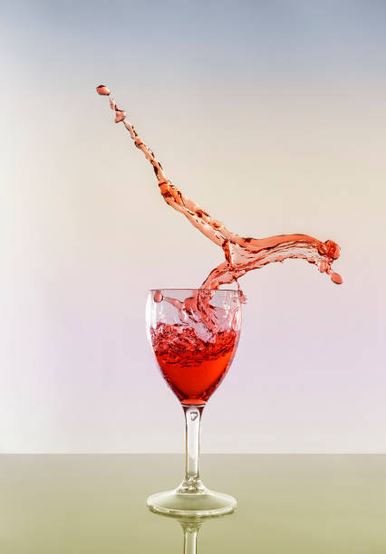 Close-Up Of Red Wine Splashing In Glass Against White Background, Annan, United Kingdom