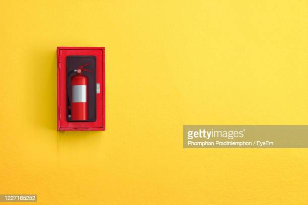 close-up of red yellow wall - fire extinguisher stock pictures, royalty-free photos & images