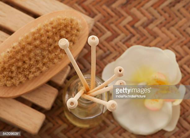 Close-up of reed diffuser with foot brush and orchid