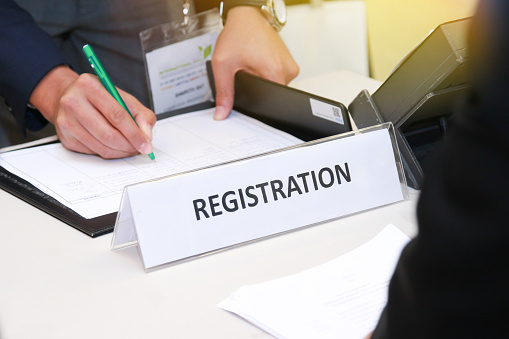 close-up of registration desk in front of conference center with Businessman Writing on the Table 1097305476