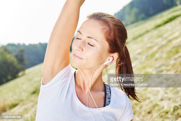 Close-Up Of Relaxed Young Woman Stretching Arms On Field