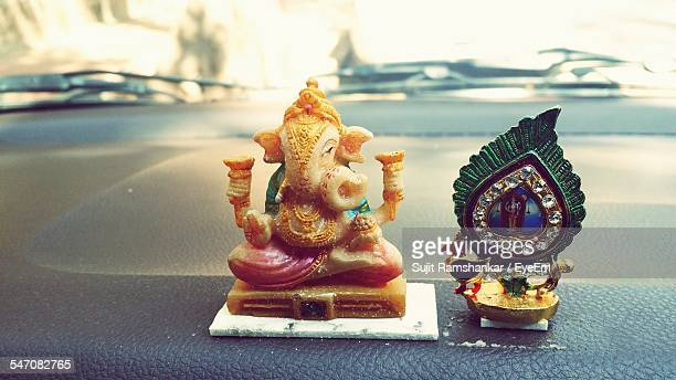 Close-Up Of Religious Figurines On Car Dashboard