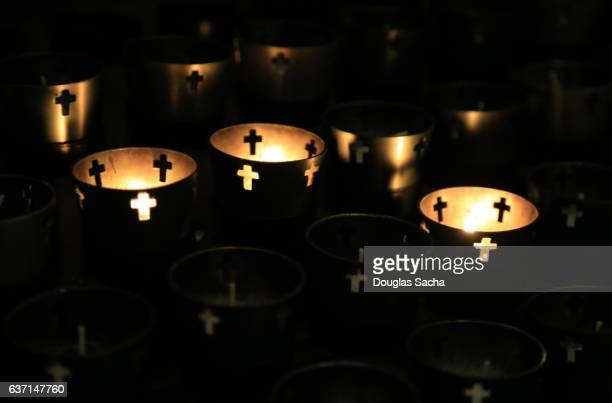 close-up of religious votive candles in a dark church - cero foto e immagini stock