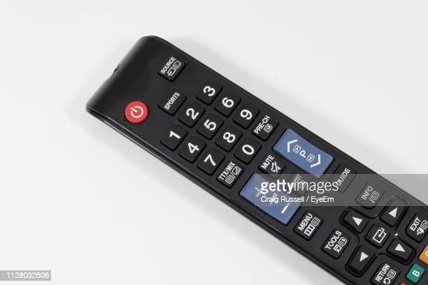 close-up of remote control against white background - afstandsbediening stockfoto's en -beelden