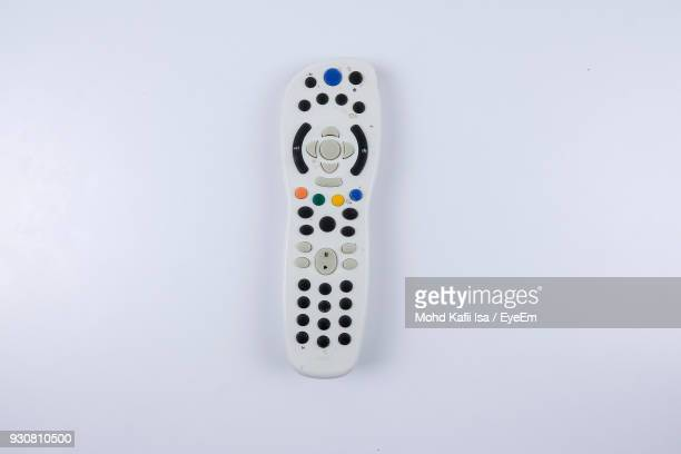 close-up of remote control over white background - afstandsbediening stockfoto's en -beelden