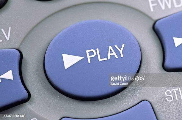 close-up of remote control 'play' button - play button stock photos and pictures