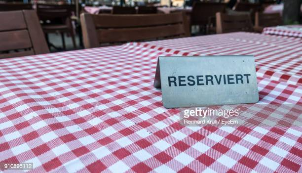 Close-Up Of Reserved Sign On Table At Restaurant
