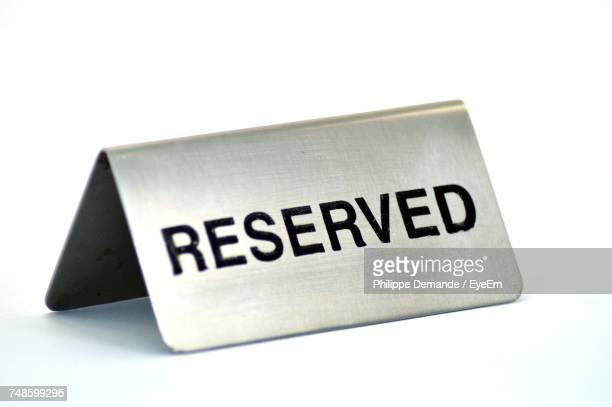 Close-Up Of Reserved Sign Over White Background