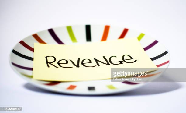 Close-Up Of Revenge Text On Paper In Plate Over White Background