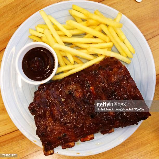 close-up of rib and french fries on plate - rib food stock photos and pictures