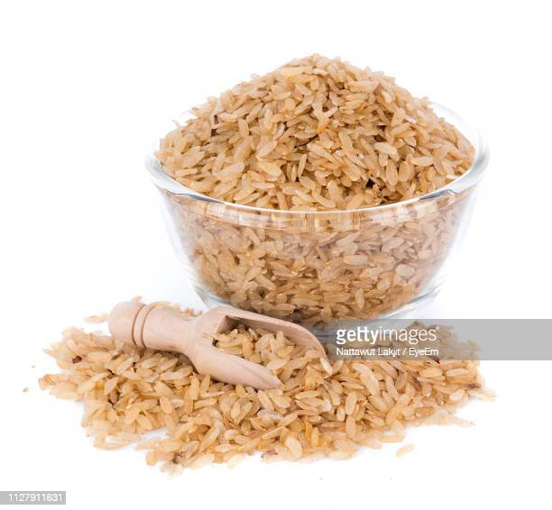 close-up of rice in bowl with wooden spoon against white background - arroz integral - fotografias e filmes do acervo