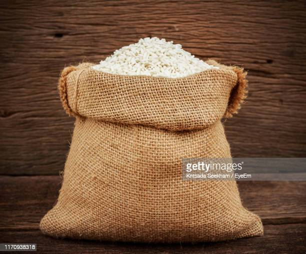 close-up of rice in sack on wooden table - 布の袋 ストックフォトと画像