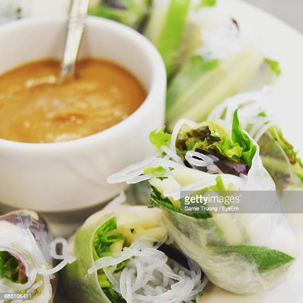 Close-Up Of Rice Paper Rolls Served With Sauce In Plate