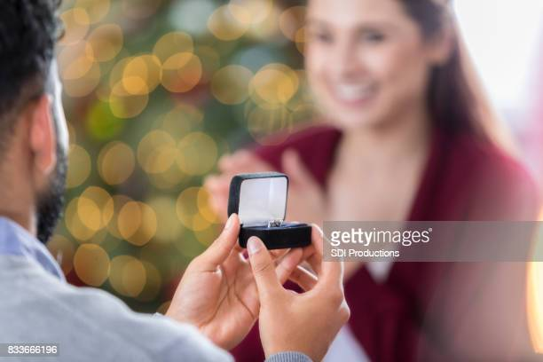 closeup of ring box as young man proposes to girlfriend - engagement ring box stock photos and pictures
