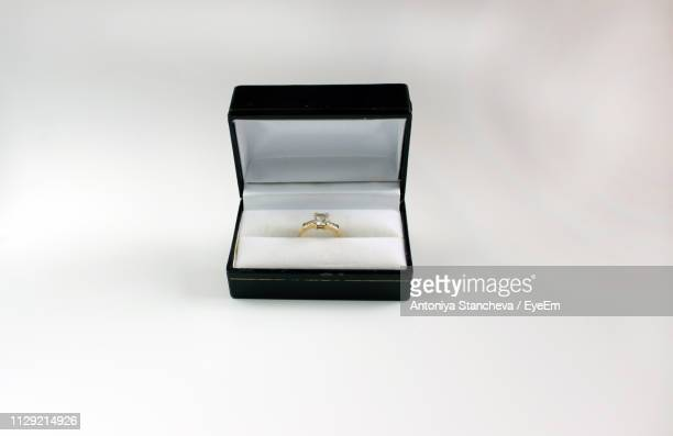 close-up of ring in box on white background - engagement ring box stock photos and pictures