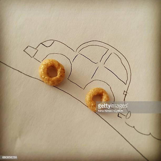 Close-up Of Ring Shaped Snacks Used As Wheel Of Car Drawing