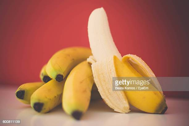 Close-Up Of Ripe Bananas On Table Against Wall