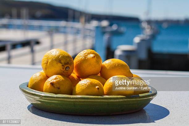 Close-up of ripe lemons on plate, pier in background