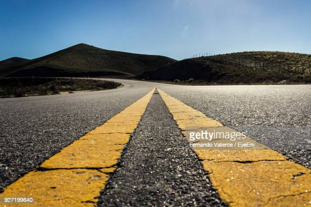 close-up of road against mountains and clear sky - dividing line road marking stock pictures, royalty-free photos & images