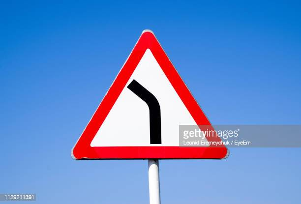 close-up of road sign against clear blue sky - road sign stock pictures, royalty-free photos & images