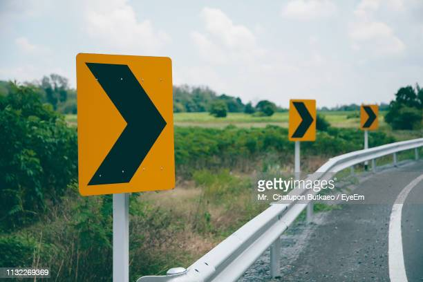 close-up of road sign against sky - curved arrows stock-fotos und bilder