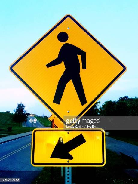 close-up of road sign against sky - pedestrian crossing sign stock photos and pictures