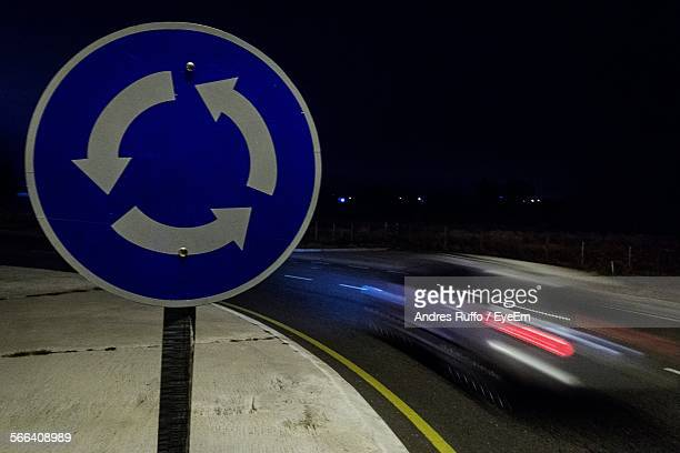 close-up of road sign by car at night - andres ruffo stock photos and pictures