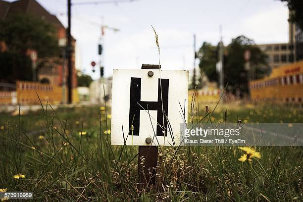Close-Up Of Road Sign On Placard In Grassy Field