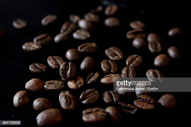 Close-Up Of Roasted Coffee Beans Against Black Background