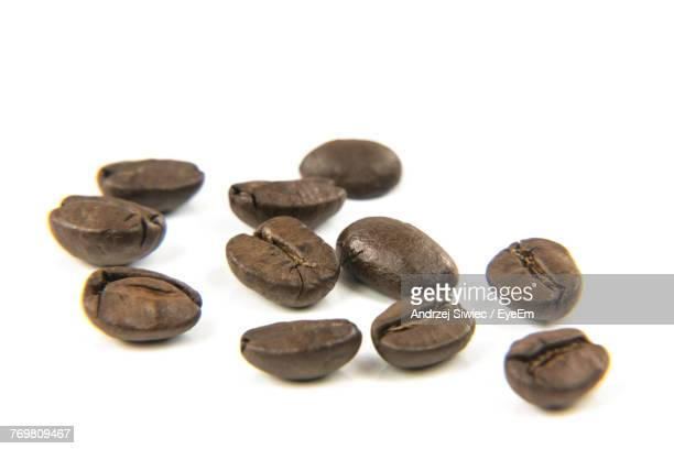 Close-Up Of Roasted Coffee Beans Against White Background