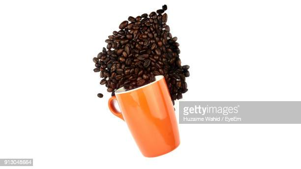 Close-Up Of Roasted Coffee Beans And Cup Over White Background