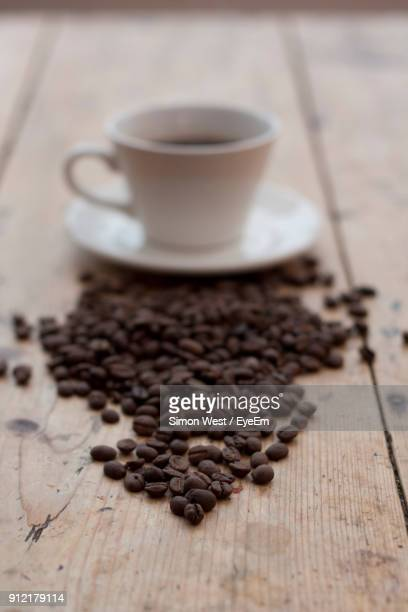 close-up of roasted coffee beans by drink on wooden table - coffee drink stock pictures, royalty-free photos & images