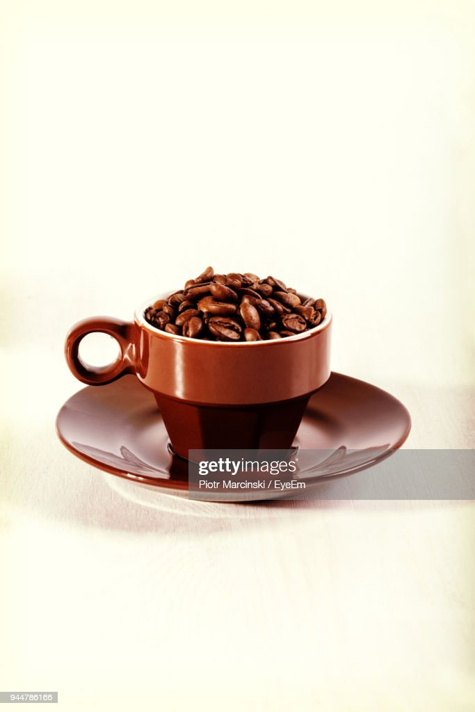 Close-Up Of Roasted Coffee Beans In Cup Over White Background : Stock Photo