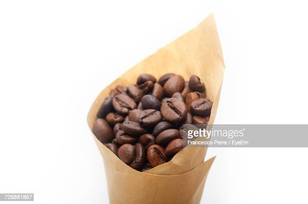 Close-Up Of Roasted Coffee Beans In Paper Cone Against White Background