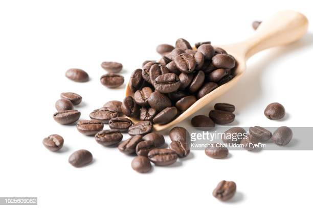 close-up of roasted coffee beans in wooden spoon against white background - roasted coffee bean stock photos and pictures